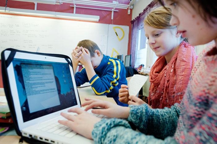 Maja Aho och Saga Midfjäll arbetar med sin text om rektorn.