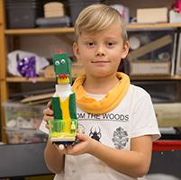 Nils, 7, med sin färdiga drakrobot.